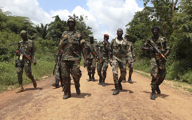 Fighters from the Republican Forces rebels walk at the village of Pekanhouebly on the border of Ivory Coast and Liberia
