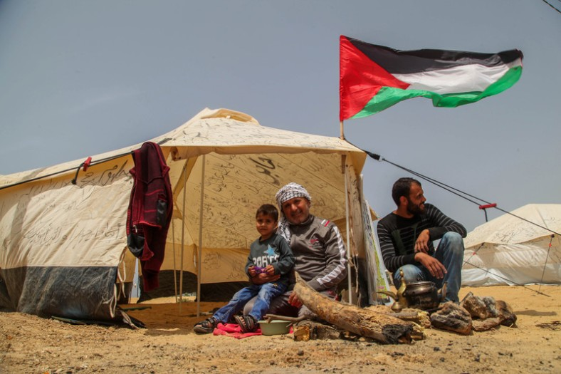 Palestinian protesters sit next to a tent during protest tents at the Israel-Gaza border where Palestinians demand the right to return to their homeland